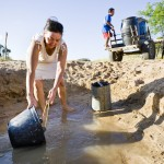 Maria Aparecida Mendes da Silva, 44 collects what little water remains from a hole in a dried out river bed.